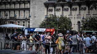 Des personnes portent un masquedans la file d'attente pour entrer au musée du Louvre, le 6 août 2020, à Paris. (STEPHANE DE SAKUTIN / AFP)