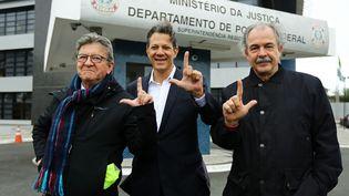 """Jean-Luc Mélenchon (à gauche), aux côtés d'anciensministre brésiliens de l'Education, Fernando Haddad (centre) et Aloizio Mercadante (droite), devant les locaux de la police de Curitiba (Brésil), le 5 septembre 2019. Ils font le signe """"L"""", en soutien à l'ex-président du BrésilLuiz Inacio Lula da Silva. (HEULER ANDREY / AFP)"""