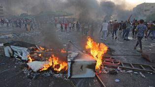 Des manifestants irakiens dénonçant la corruption des dirigeants brûlent des objets pour bloquer une route du centre de Bagdad, le 3 octobre 2019. (AHMAD AL-RUBAYE / AFP)