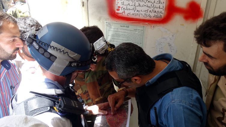 Un membre de l'opposition syrienne discute avec desexperts de l'ONU qui inspectent un site de labanlieue de Damas,où des roquettessont tombées le 28 août 2013. (AFP PHOTO / MOHAMED ABDULLAH / SHAAM NEWS NETWORK)