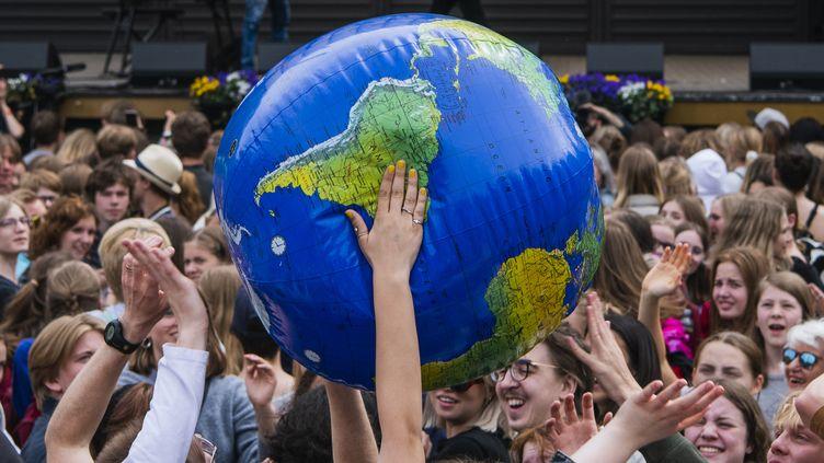 """Des participants à la """"grève mondiale pour le futur"""" tiennent une planète gonflable dans leurs mains, le 24 mai 2019, à Stockholm (Suède). (JONATHAN NACKSTRAND / AFP)"""