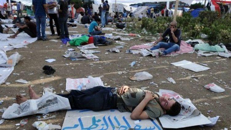 """Samedi 9 juillet 2011, un jeune dort place Tahrir au Caire sur un Carton disant """"le peuple veut renverser le régime"""". (AFP - Mohamed Hossam)"""