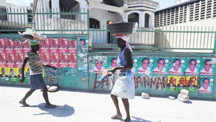 Des Haïtiens passent devant des affiches des deux candidats au deuxième tour de la présidentielle (19 mars) (AFP / Thony Belizaire)