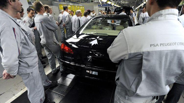 Des ouvriers de l'usine PSA de Sochaux (Franche-Comté)rassemblés autour de la dernière Peugeot 607 produit dans la même usine, le 4 mars 2009. (SEBASTIEN BOZON / AFP)