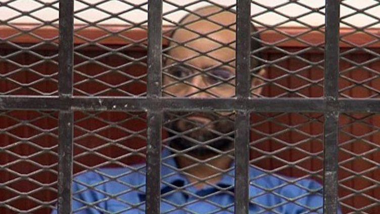 Seif al-Islam Kadhafi, le fils de l'ancien dictateur libyen Moammar, dans le box des accusés dans le tribunal de la ville de Zintan, le 2 mai 2013, où il comparaissait pour tentative de contact illégal avec l'étranger et «complot contre la sécurité de l'Etat». (AFP PHOTO/STR)