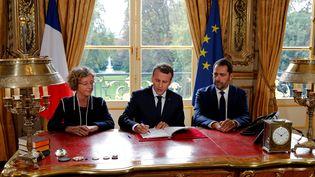 Le président de la République, Emmanuel Macron, aux côtés de Muriel Pénicaud, la ministre du Travail, et de Christophe Castaner, porte-parole du gouvernement, lors de la signature des ordonnances réformant le droit du travail, vendredi 22 septembre à l'Elysée. (PHILIPPE WOJAZER / POOL)