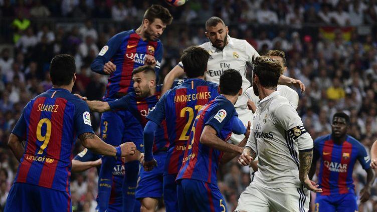 Le défenseur du FC Barcelone Gerard Piqué (à gauche) et l'attaquant du Real Madrid Karim Benzema (à droite) à la lutte lors du Clasico disputé entre les deux équipes le 23 avril dernier au stade Santiago-Bernabeu (3-2 pour le Barça).  (PIERRE-PHILIPPE MARCOU / AFP)