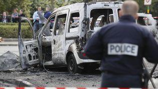 Un officier de police monte la garde près d'un véhicule de police incendié à Viry-Châtillon (Essonne) le 8 octobre 2016. (THOMAS SAMSON / AFP)