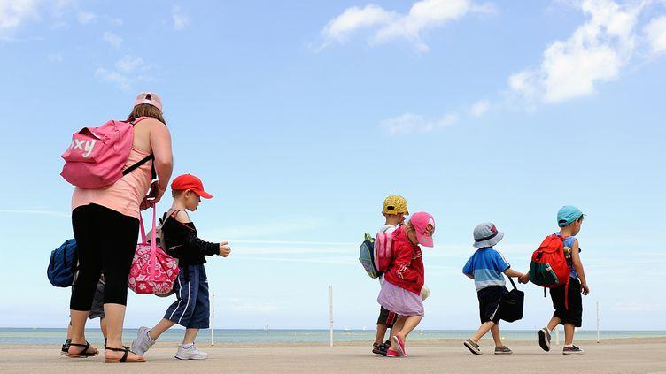 Une animatrice de colonie de vacance avec des enfants, le 25 juillet 2013, sur la plage de Bray-Dunes (Nord). (PHILIPPE HUGUEN / AFP)