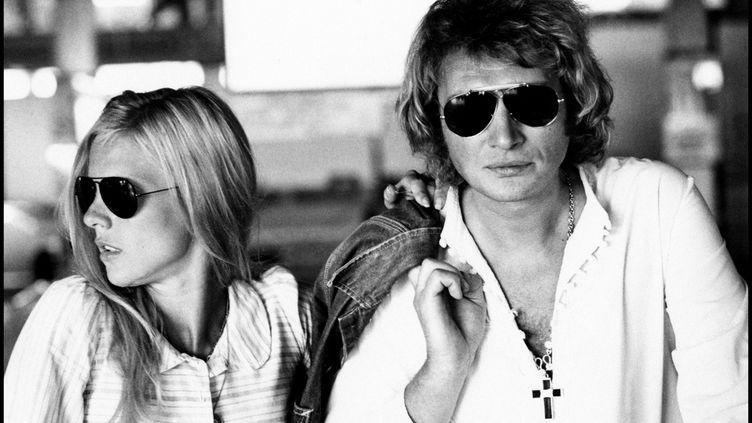 Johnny Hallyday, veste en jean sur l'épaule et croix au cou, pose avec Sylvie Vartan à MIlan en 1973. (LEEMAGE / AFP)