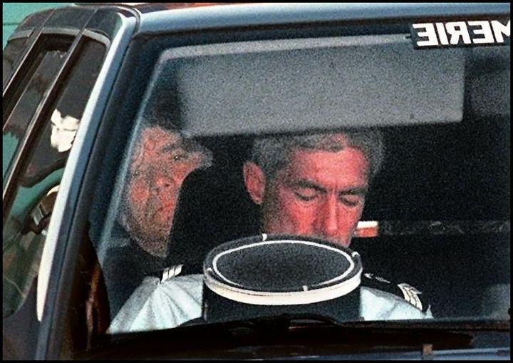 Assis à l'arrière d'une voiture de la gendarmerie, l'homme d'affaires arrive, le 22 mai 1997, au palais de Justice de Marseille, où se déroule le procès des comptes du club marseillais. (CLAUDE PARIS / AFP)