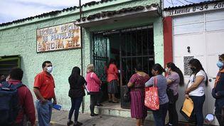 Des habitants deChimaltenango, au Guatemala, à l'entrée d'une école, le 22 février 2021. (JOHAN ORDONEZ / AFP)
