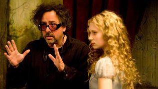"""Tim Burton et son actrice Mia Wasikowska sur le tournage du premier volet d'""""Alice au Pays des Merveilles"""", sorti en 2010.  (ARCHIVES DU 7EME ART / PHOTO12 / AFP)"""