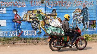 "Un motard passe devantungraffiti sur un mur deKibera, le plus grand bidonville de Nairobi, la capitale kényane,vsur lequel on peut lire ""Pamoja tuangamize Corona"", qui signifie :""Combattons le corona ensemble""(13 août 2020). (SIMON MAINA / AFP)"