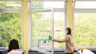 Une élève ouvre les fenêtres de sa classe à Hambourg (Allemagne), le 19 octobre 2020. (DANIEL BOCKWOLDT / DPA / AFP)