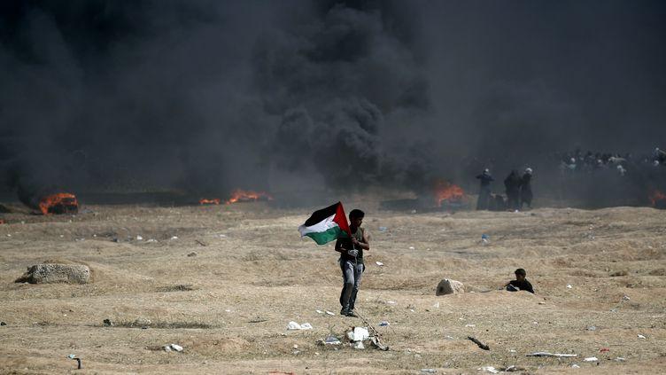 Un Palestinien tient un drapeau près dela frontière entre Israël etla bande de Gaza, le 14 mai 2018. (THOMAS COEX / AFP)