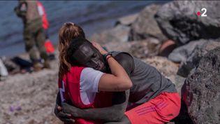 Une bénévole de la Croix rouge réconforte un migrant sur une plage de l'enclave espagnole de Ceuta, le 20 mai 2021. (FRANCE TELEVISIONS)
