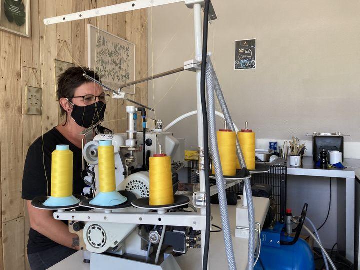 Derrière l'une des machines à coudre, Christhine, prototypiste, attend l'arrivée de Tadej Pogacar. (Adrien Hémard / franceinfo:sport)