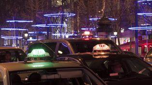 Des taxis parisiens sur les Champs-Elysées, en décembre 2011. (JACQUES LOIC / PHOTONONSTOP / AFP)