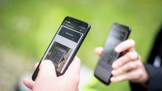 Une personne scanne le QR code d'une autre grâce à son smartphone en Bavière (Allemagne), le 14 mai 2021 (illustration). (MATTHIAS BALK / DPA)