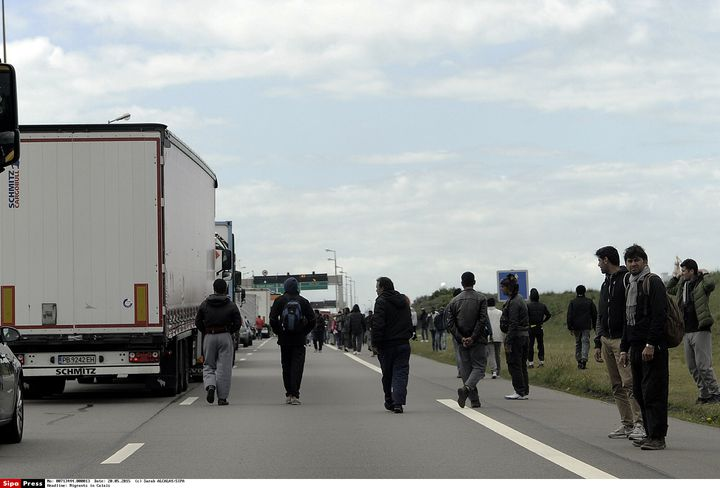 Des migrants profitent d'un embouteillage aux abords du port de Calais pour tenter de monter à bord de camions en partance pour l'Angleterre, le 20 mai 2015. (SARAH ALCALAY / SIPA)