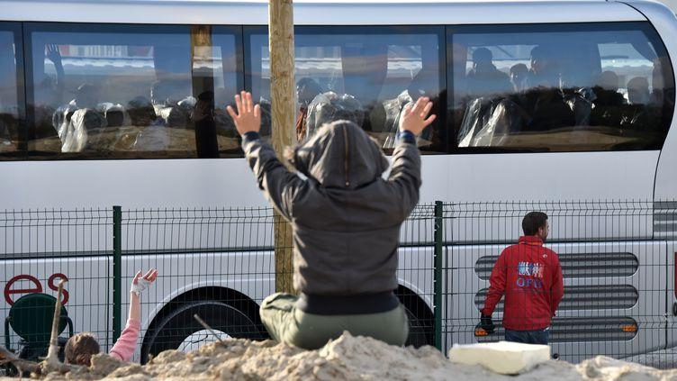 """Un migrants saluant le départs de mineurs isolés de la """"jungle"""" de Calais (Pas-de-Calais), le 2 novembre 2016. (PHILIPPE HUGUEN / AFP)"""