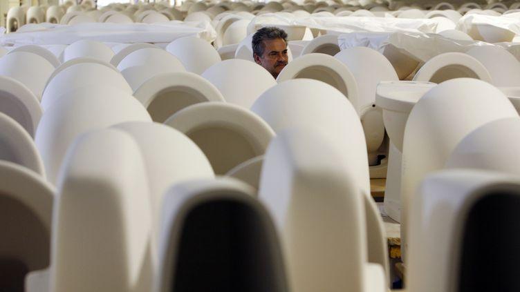 Un employé au milieu de sanitaires produits par Villeroy& Boch, à Mettlach, en Allemagne.Villeroy& Boch estrestée une entreprise de famille depuisplus de 250 ans. (FRANK RUMPENHORST / DPA / AFP)