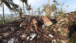 Un petit garçon joue sur les ruines de sa maison, à Port-Vila, au Vanuatu, le 16 mars 2015. (DAVE HUNT / AP / SIPA)