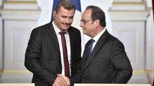 Hagi Hasan Brita, président du conseil local des quartiers d'Alep-Est (à gauche), en compagnie de François Hollande, à Paris, le 19 octobre 2016. (ALAIN JOCARD / AFP)