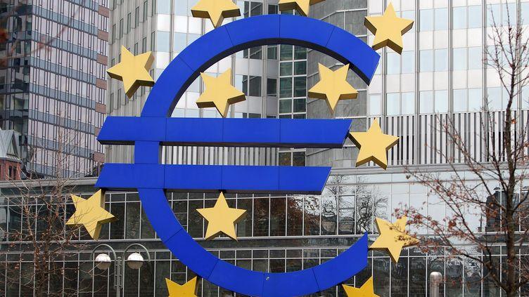 Une sculpture avec le logo de l'euro, devant le siège de la Banque centrale européenne, à Francfort (Allemagne), le 2 décembre 2014. (DANIEL ROLAND / AFP)