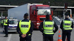 Des policiers contrôlent des camions, au niveau du péage de La Turbie (Alpes-Maritimes), sur l'A8, le 13 novembre 2015. (ANNE-CHRISTINE POUJOULAT / AFP)