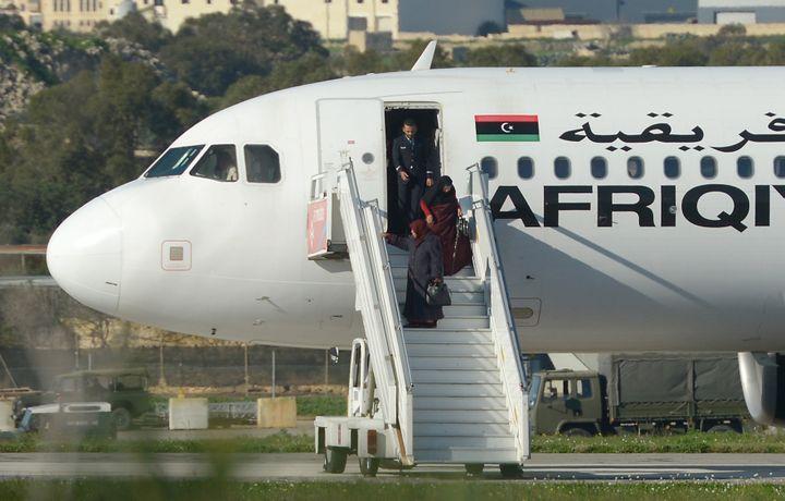 Des passagers sont évacués de l'avion libyen détourné vers Malte, le 23 décembre 2016, à La Valette (Malte). (MATTHEW MIRABELLI / AFP)