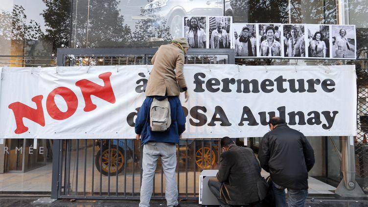 Des salariés de PSA installent une banderole lors d'une manifestation devant des locaux du groupe, à Paris, le 25 octobre 2012. (FRANCOIS GUILLOT / AFP)