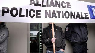 """Un policier tient une pancarte du syndicat Alliance police nationale lors d'une manifestation contre la """"haine des flics"""" à Nantes en mai 2016 (photo d'illustration). (JEAN-SEBASTIEN EVRARD / AFP)"""
