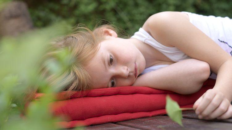 Allongée, la fillette semble s'ennyuer et rêvasser. (THIERRY FOULON / MAXPPP)