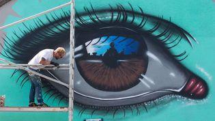 """L'artiste My Dog Sighs (littéralement, """"mon chien soupire"""") peint sur la Bristol beer factory au Festival Upfest, le 25 juillet 2015  (LNP/REX Shutterstock/SIPA)"""
