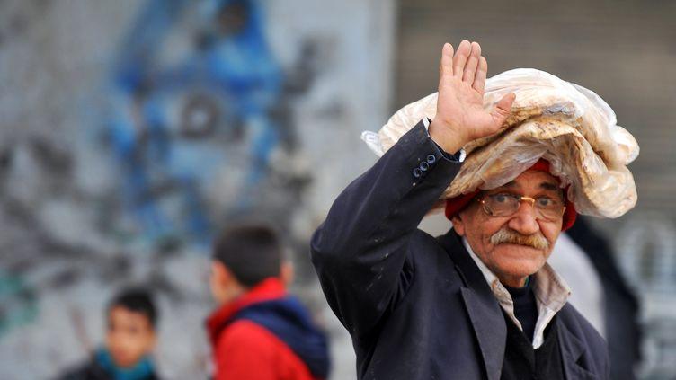 Un vieil homme salue le photographe après être allé chercher du pain, le 14 février 2013 à Alep (Syrie). (BULENT KILIC / AFP)