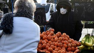 Un marchand de fruits et légumes porte un masque sur le marché de Crépy-en-Valois (Oise), le 1er mars 2020. (FRANCOIS LO PRESTI / AFP)