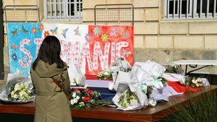Une femme se recueille, le 26 avril 2021, devant un message et des fleurs en hommage àStéphanie Monfermé, la fonctionnaire de police tuée lors d'une attaque au couteau au commissariat de Rambouillet (Yvelines). (BERTRAND GUAY / AFP)