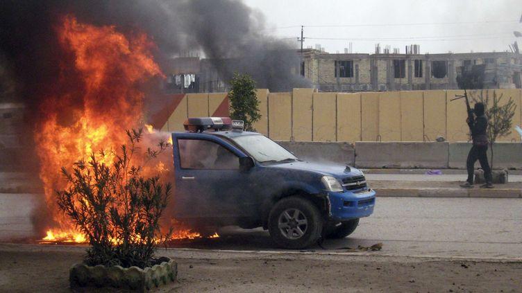 Un combattant d'Al-Qaïda monte la garde près d'un véhicule de la police incendié, à Fallouja (Irak), le 1er janvier 2014. (AP / SIPA )
