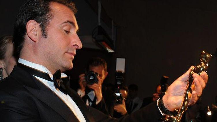 Jean Dujardin, meilleur rôle principal masculin aux Oscars, regarde sa statuette (26 février 2012)  (Valerie Macon / AFP)