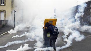 Un manifestant se protège derrière une poubelle à Rennes (Ille-et-Vilaine), le 17 mai 2016 pendant la manifestation contre la loi Travail, alors que des grenades lacrymogènes tombent à ses pieds. (DAMIEN MEYER / AFP)