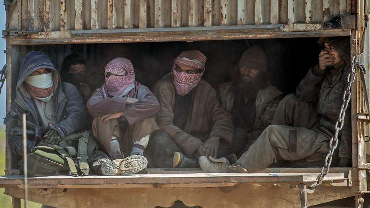 Des hommes identifiés comme des combattants du groupe terroriste Etat islamique dans un camion, le 20 février 2019,àBaghouz(Syrie). (BULENT KILIC / AFP)