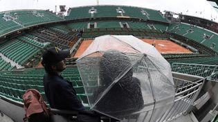 Un spectateur sous un parapluie dans le court vide Philippe Chartier de Roland Garros, à Paris, le 30 mai 2016. (MIGUEL MEDINA / AFP)
