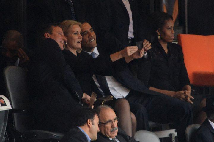 David Cameron, Helle Thorning-Schmidt et Barack Obama (de gauche à droite) se prennent en photo, à côté de Michelle Obama, lors de l'hommage à Nelson Mandela, le 10 décembre 2013. (ROBERTO SCHMIDT / AFP)