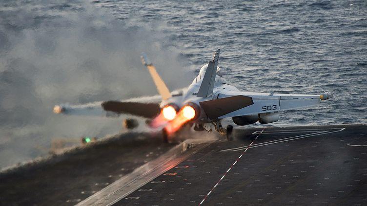 """Un avion de chasse américain décolle du porte-avion """"USS Carl Vinson"""", dans le golfe d'Arabie, pour aller effectuer des frappes aériennes en Syrie, le 28 octobre 2014. (US NAVY / REUTERS)"""