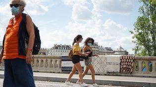 Des femmes portent un msaque sanitaire surun pont de l'île Saint-Louis, à Paris, le 15 août 2020. (MYRIAM TIRLER / HANS LUCAS / AFP)
