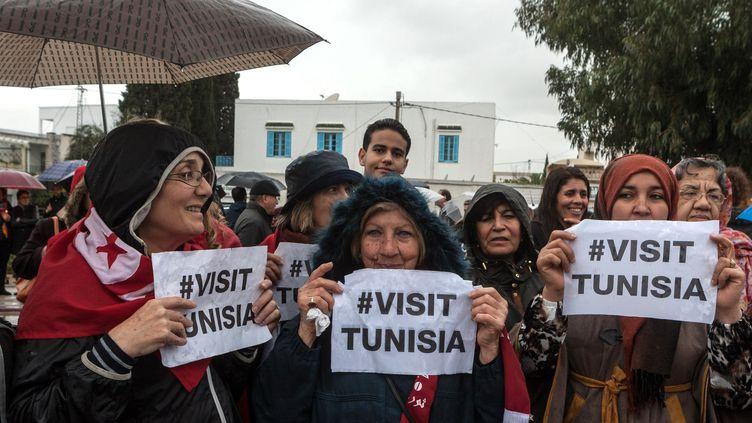 """Des manifestants brandissent des pancartes """"visitez la Tunisie"""", lors d'un rassemblement devant le musée du Bardo à Tunis, le 24 mars 2015. (AMINE LANDOULSI / ANADOLU AGENCY / AFP)"""