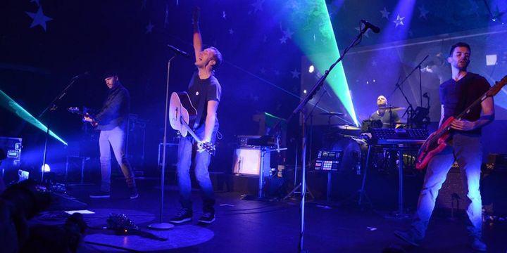 Jonny Buckland (guitare), Chris Martin (chant, guitare), Will Champion (batterie) et Guy Berryman (basse) sur la scène du Casino de Paris le 28 mai 2014  (Page Facebook Coldplay)