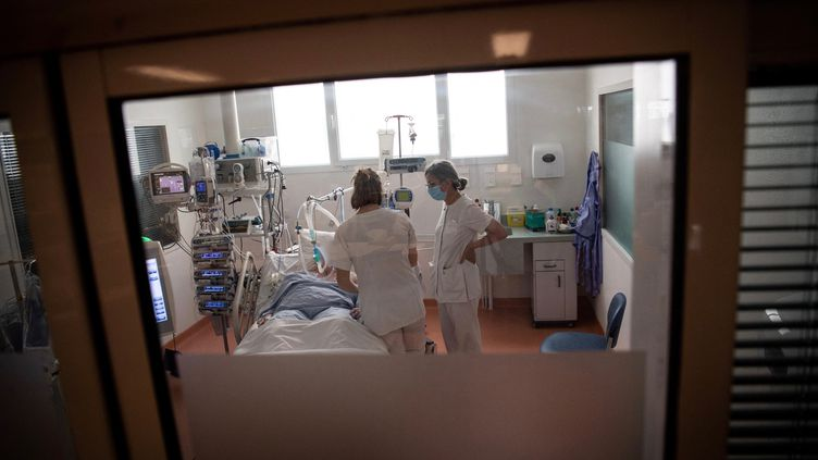 Des soignantes s'occupent d'un patient infecté par le Covid-19 à Vannes le 20 avril 2021. Photo d'illustration. (LOIC VENANCE / AFP)